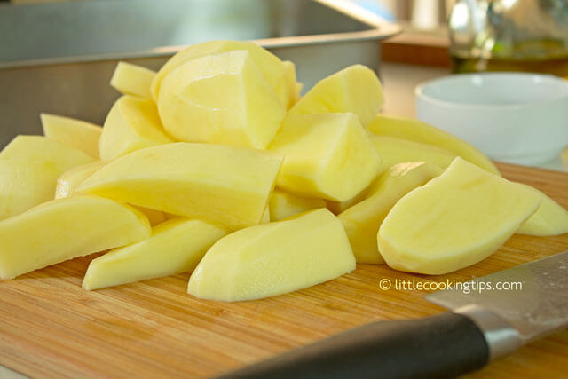 Freshly cut potato wedges on the wooden cutting board